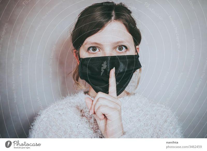 Junge Frau, die eine Gesichtsmaske trägt und um Schweigen bittet Bund 19 COVID Coronavirus Virus Atem Pandemie Mundschutz Stille geheim Lügen Windstille Geduld