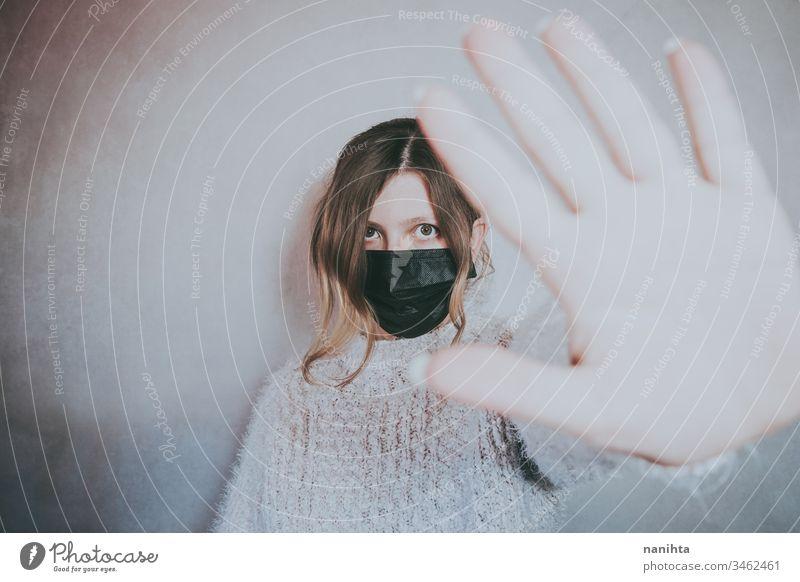 Junge Frau, die eine Maske trägt und ihre Hand für soziale Distanz legt Bund 19 COVID Coronavirus Virus Atem Pandemie Mundschutz Krankheit infiziert stoppen