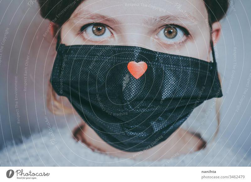 Junge Frau trägt eine Maske mit einem roten Herz Bund 19 COVID Coronavirus Virus Atem Pandemie Mundschutz Krankheit Hoffnung Liebe Hilfsbereitschaft Solidarität