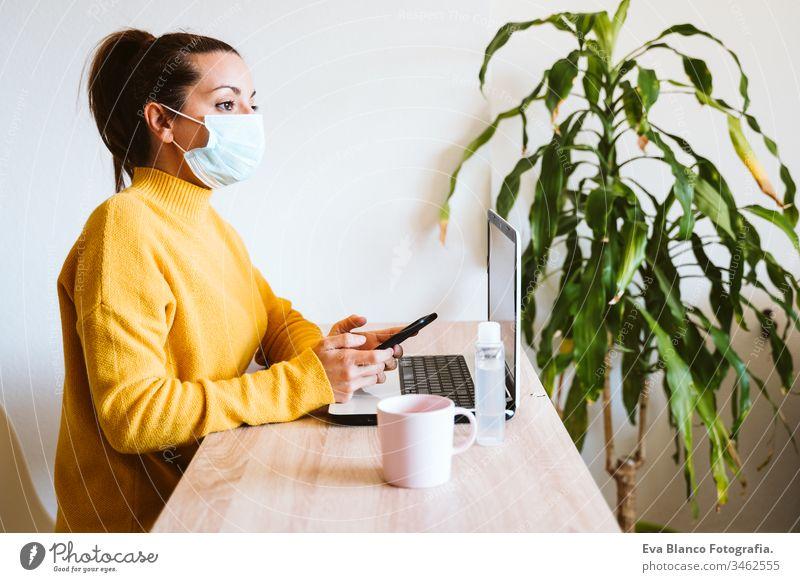 junge frau, die zu hause am laptop arbeitet und eine schutzmaske trägt. arbeiten sie von zu hause aus, bleiben sie während des coronavirus covid-2019 concpt sicher