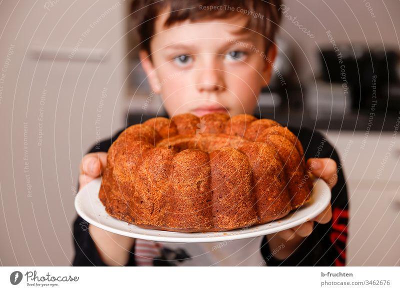 Kind hält Teller mit Kuchen Gugelhupf süß Farbfoto lecker Innenaufnahme Backwaren Süßwaren Dessert halten frisch gebacken zeigen stolz Küche helfen Junge Hand
