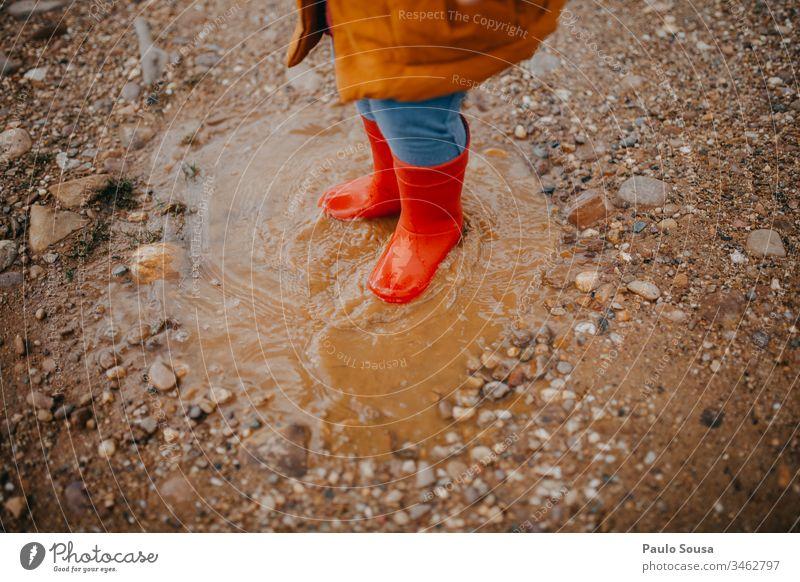 Kinderfüße in roten Gummistiefeln über einer Pfütze Stiefel Regen nass Außenaufnahme Wetter Farbfoto Mensch Freude Wasser dreckig Kindheit schlechtes Wetter