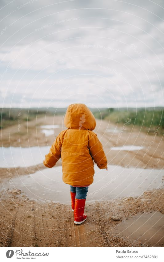 Rückansicht eines in einer Pfütze laufenden Kindes mit orangefarbener Jacke Gummistiefel rot nass Außenaufnahme Farbfoto Regen Mensch Freude Wasser Spielen