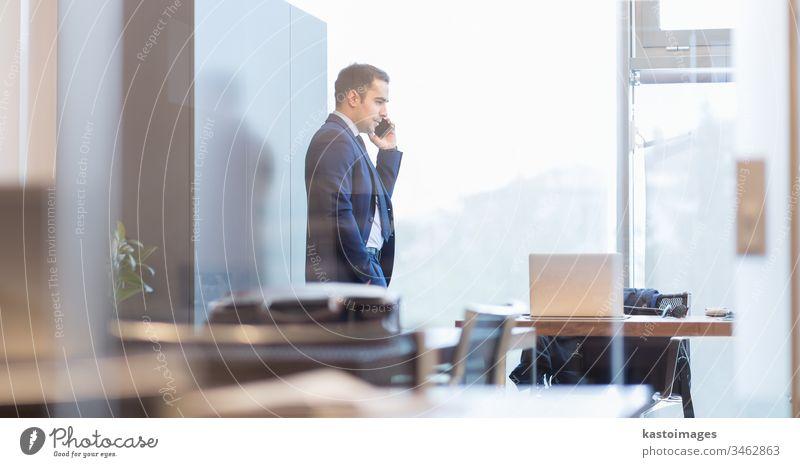 Geschäftsmann spricht mit einem Mobiltelefon, während er durch ein Fenster schaut. Business Telefon Büro korporativ Unternehmer professionell männlich Person
