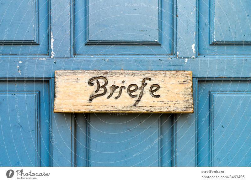 """""""Schreib mal wieder"""" schien die hölzerne Briefkastenklappe in der blauen Tür zu sagen Postkasten Briefe blauer Hintergrund Holz Schreibschrift Haus"""