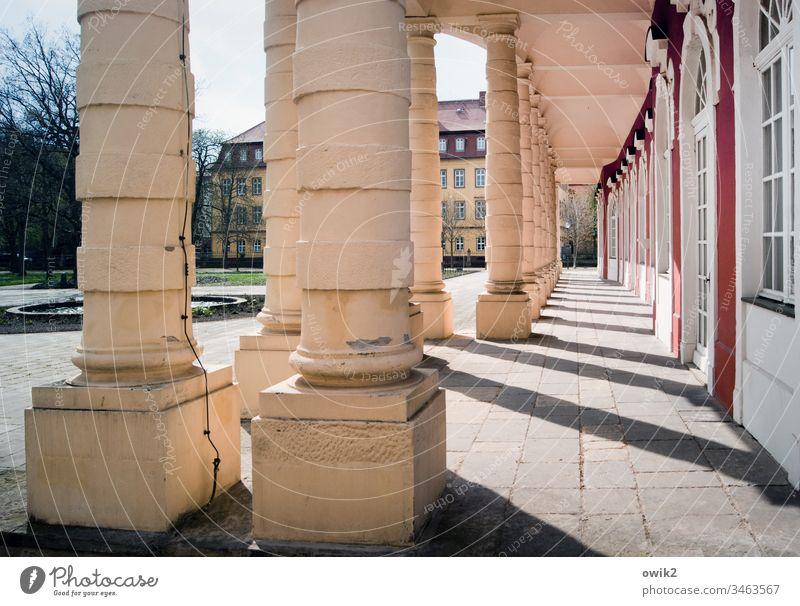 Kolonnaden Säulen Schloss Gang lustwandeln repräsentativ Architektur Gebäude Menschenleer Schatten Licht alt Bauwerk Sehenswürdigkeit historisch Stein Fassade