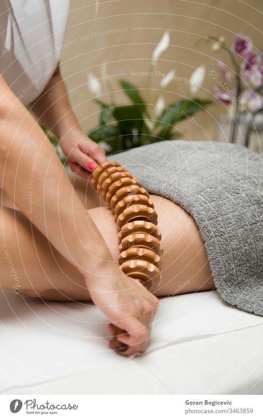 Maderotherapeutische Anti-Cellulite-Massage mit einem Massageroller aus Holz Erwachsener Körper Pflege tief Frau Hand Handgriff Gesundheit Bein Beine Lifestyle