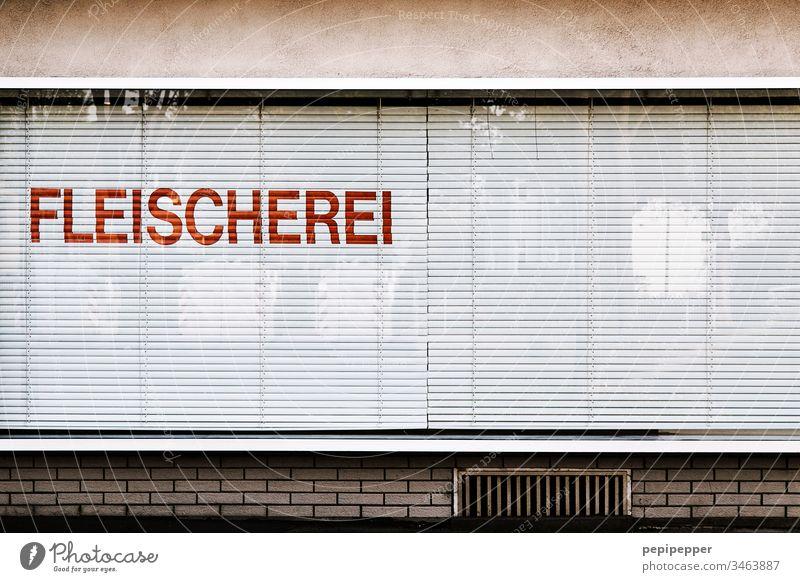 Schaufenster Fleischerei Fenster Ladengeschäft Menschenleer Außenaufnahme Haus Fassade Gebäude Gedeckte Farben Wand alt Fensterscheibe Buchstaben Wurstwaren
