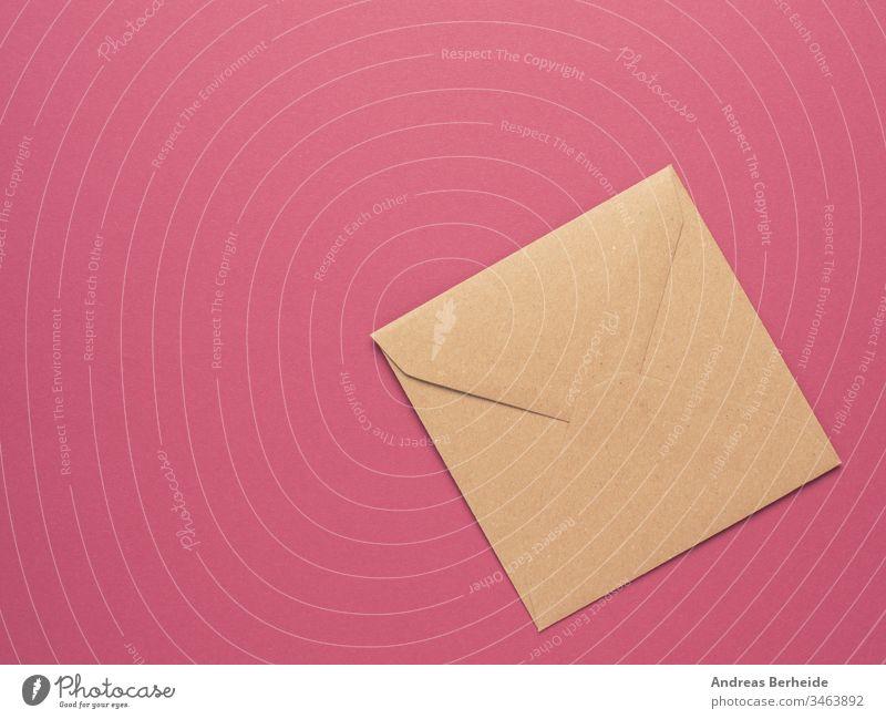 Ein Umschlag aus Recyclingpapier auf rotem Hintergrund mit Kopierfeld Kuvert Papier vereinzelt Brief Post blanko weiß Beitrag Nachricht Mitteilung Korrespondenz