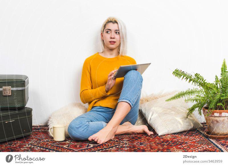 Junge Frau benutzt einen Tablet-Computer, während sie zu Hause auf dem Boden sitzt. Tablette 1 jung heimwärts schön Erwachsener Sitzen Glück