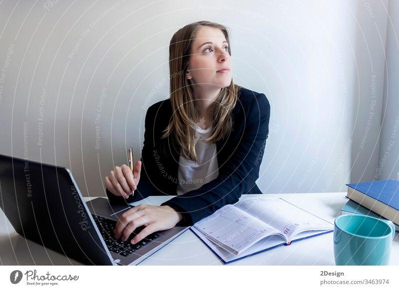 Lächelnde Jungunternehmerin sitzt zu Hause und arbeitet mit ihrem Laptop jung Frau Tisch professionell 1 Geschäftsfrau Sitzen Technik & Technologie Computer