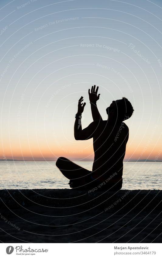 Silhouette eines Mannes, der bei Sonnenuntergang am Strand zu Gott betet Erwachsener allein Waffen betteln Glaube Geständnis beschwören Kultur Depression