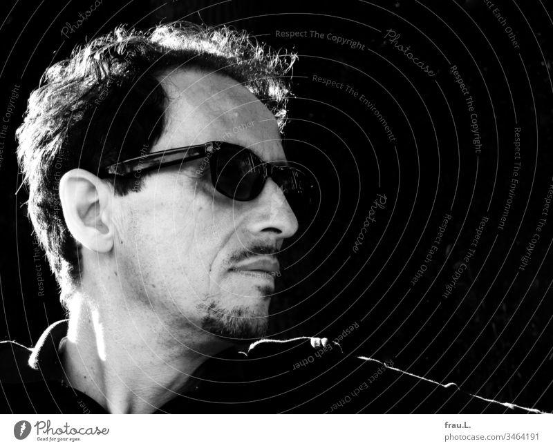Durch die markante Sonnenbrille sah der markante Mann markant in die Ferne. Mensch Porträt Schwarzweißfoto Bart Erwachsene Tag Außenaufnahme Coolness attraktiv