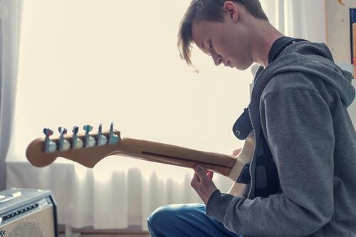Männlicher Teenager spielt in seinem Zimmer auf einer Elektrogitarre. teenager Gitarre Phantasie Sonnenlicht Jugendkultur Fenster Raum Quarantäne covid-19 Virus