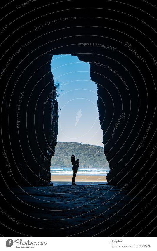 Frau in Höhle am Strand Neuseeland Identität Ferien & Urlaub & Reisen Stimmung Tourismus Farbfoto Außenaufnahme Licht Schatten Silhouette Unschärfe Natur