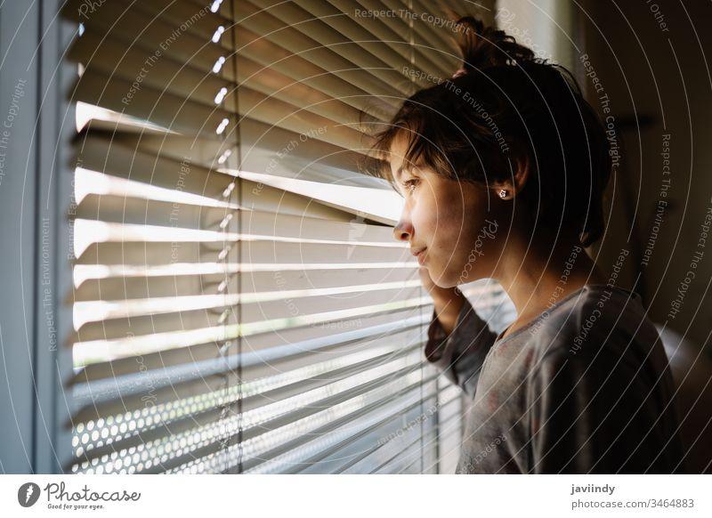 Neunjähriges Mädchen schaut durch die Jalousien aus dem Fenster zu Hause bleiben jung Frau heimwärts Quarantäne Person Gesicht Tag Raum Kaukasier schön Porträt