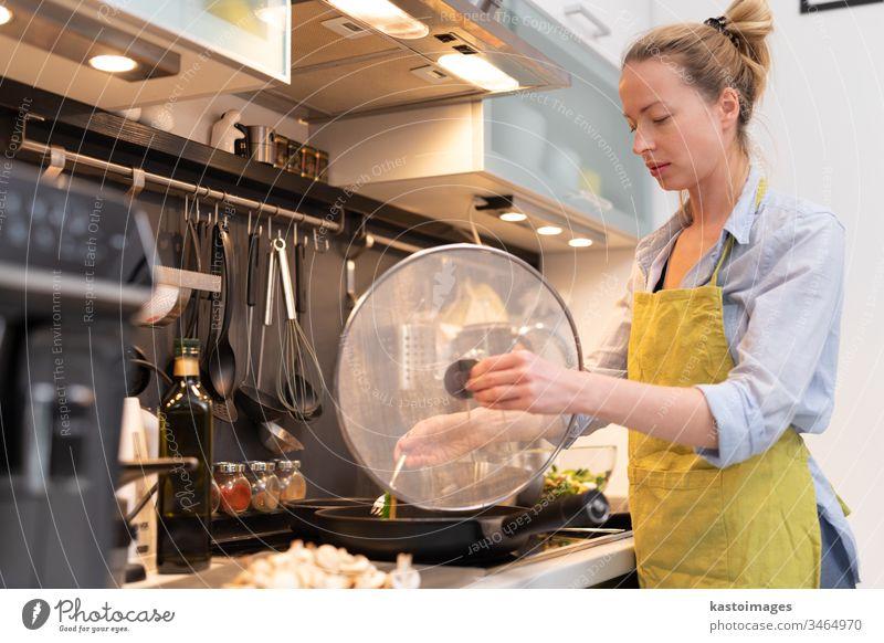 Bleiben Sie zu Hause Hausfrau Frau kocht in der Küche, rühren Braten in einem Kochtopf, Vorbereitung der Nahrung für das Abendessen der Familie. heimwärts
