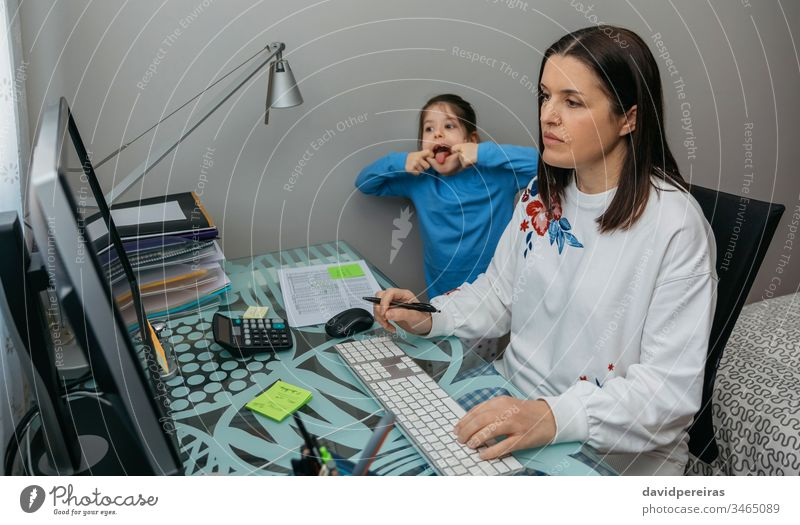 Telearbeiterin bei einer Videokonferenz mit ihrer Tochter, die eine Grimasse zieht Vereinbarkeit von Familienarbeit Coronavirus Kind Grimassen schneiden lustig