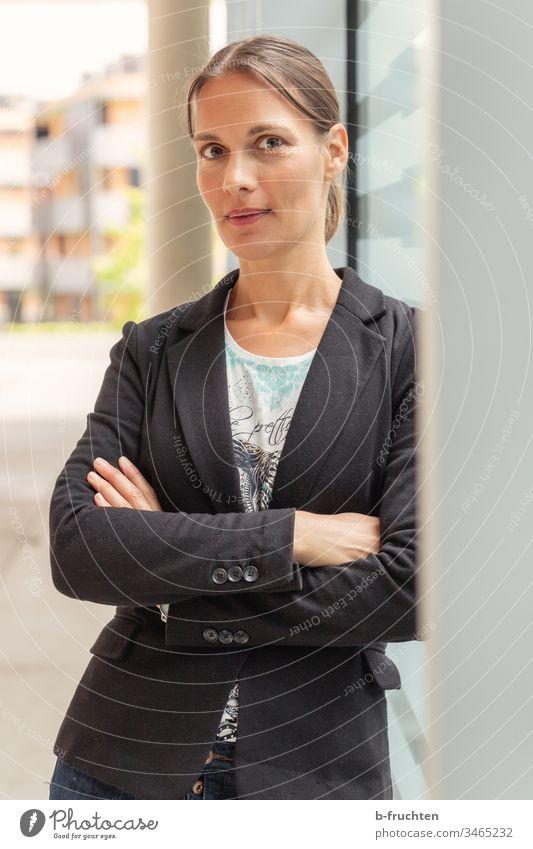 Frau stehend bei Betonsäule frau Sakko Junge Frau Porträt feminin Außenaufnahme Erwachsene Farbfoto Schwache Tiefenschärfe Business warten Bürogebäude Office