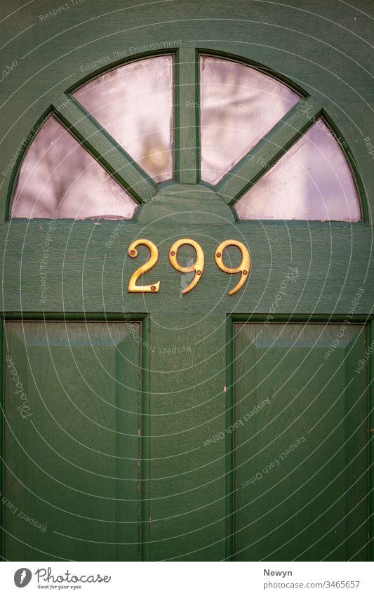 Hausnummer 299 auf grüner Holzhaustür mit Glasscheiben Halbkreis Adresse britannien klassisch stilvoll abschließen Nahaufnahme Dekoration & Verzierung Design