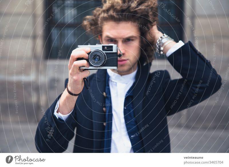 Junger Mann fotografiert mit einer alten Retrofilmkamera. Selektiver Fokus. Fotokamera altehrwürdig Hipster retro Ferien & Urlaub & Reisen Stil Tourist
