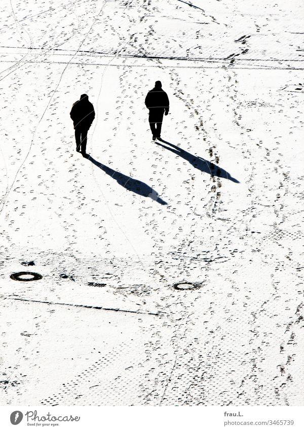 Wie geklont und sich doch fremd stapften die beiden Männer im Schnee aneinander vorbei. Winter Platz Mann Schwarzweißfoto kalt Spuren Schatten Sonnenlicht