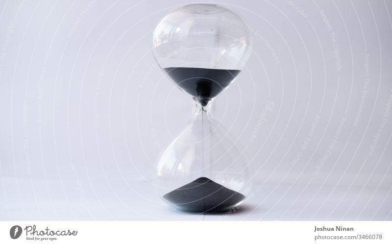 Sanduhr mit auslaufendem schwarzen Sand Hintergrund schwarzer Sand Sanduhr aus schwarzem Sand Uhr Konzept Countdown Frist Eieruhr fließend Zukunft Glas Stunde
