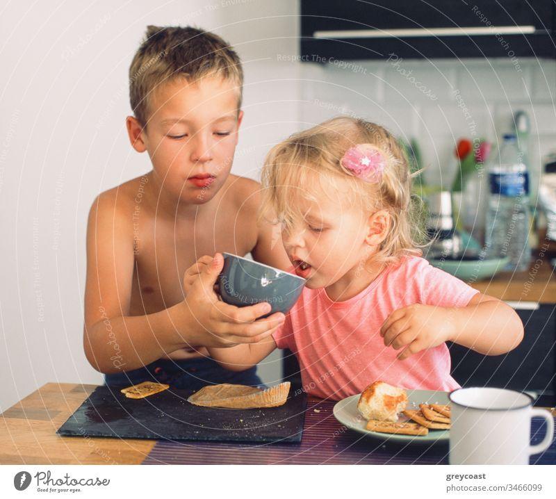 Der ältere Bruder kümmert sich um die jüngere Schwester und hilft ihr beim Trinken aus der Tasse während des Frühstücks. Alltägliche Morgenmomente Kinder Pflege