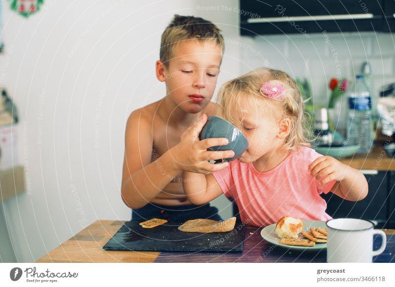 Älterer Bruder und kleine Schwester beim Frühstück in der Küche. Vorsichtig Junge hilft Mädchen trinken aus der Tasse Kinder Morgen Pflege Tee Mahlzeit