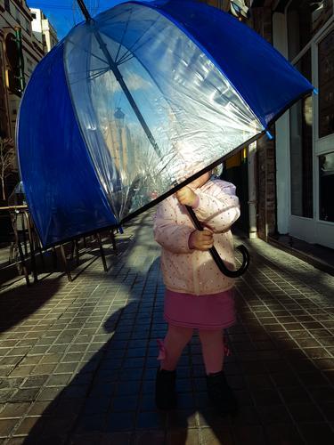 Kleines Mädchen mit großem Regenschirm gegen die Sonne auf der Straße. Kind liebt es, unter zu verstecken Tierhaut Kleinkind Herbst außerhalb fallen Dame