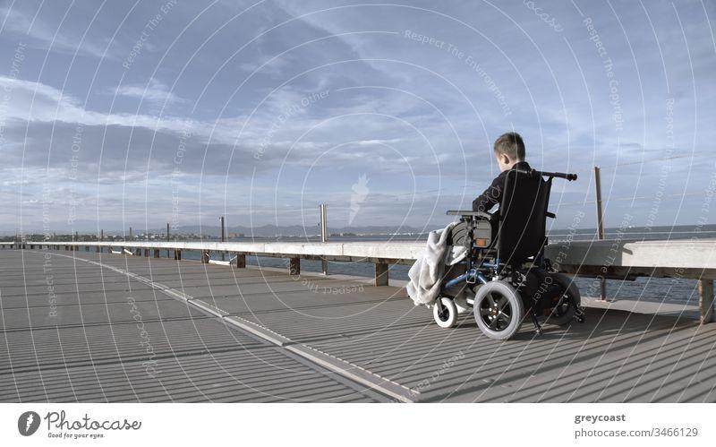 Behindertes Kind ist einsam in dieser großen aktiven Welt. Behinderter Junge im Rollstuhl draußen allein, Aufnahme in Grautönen Handicap deaktiviert Depression
