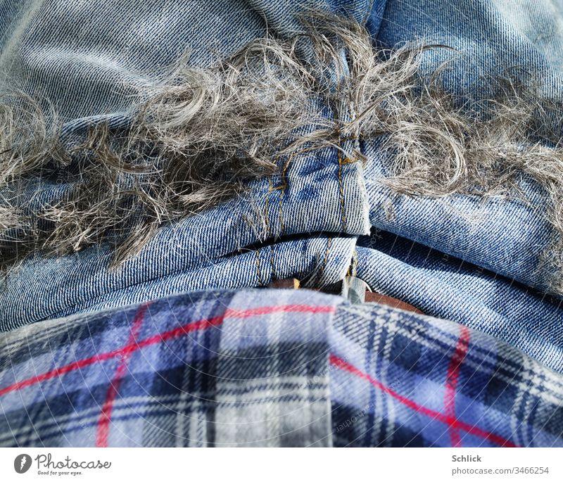 Die Haare sind ab und liegen auf dem Schoß, Coronafrisur Haare schneiden Jeans Detail Hose Nahaufnahme Hemd Bekleidung Vogelperspektive blau grau schwarz rot