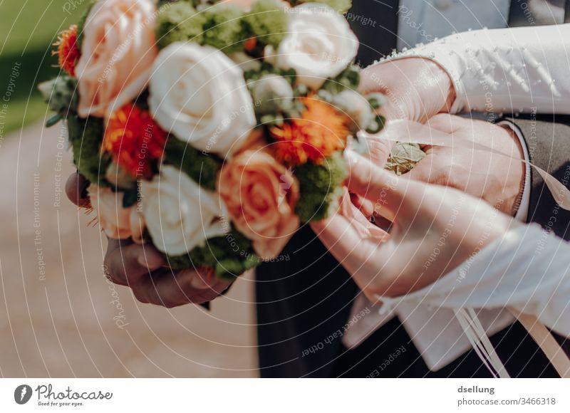Braut und Bräutigam halten gemeinsam den Brautstrauß Hochzeitszeremonie Zukunft Sicherheit Romantik Treue Liebe weiß orange grün gelb Wärme Klischee Kitsch