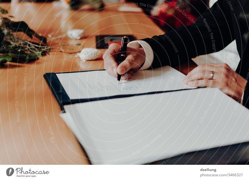 Der Bräutigam unterschreibt die Heiratsurkunde beim Standesamt Veranstaltung hochzeitlich liebevoll Planer Braut Brautkleid formal Vereinbarung symbolisch