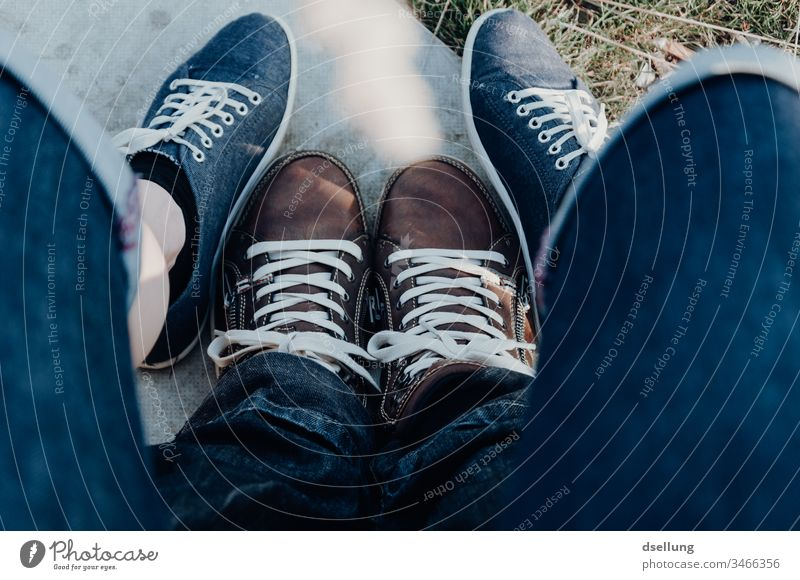 Junges Paar zeigt entspannt seine Füße in modernen Schuhen und bilden damit eine begeisternde Formation Vogelperspektive Starke Tiefenschärfe Sonnenlicht
