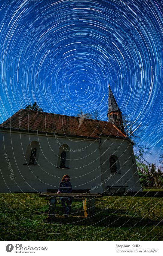 Sternennacht bei klarem Himmel, lang belichtetes Foto mit kreisrunden Sternenspuren Polaris im Fokus und einer Kapelle im Vordergrund. Kirche Nacht