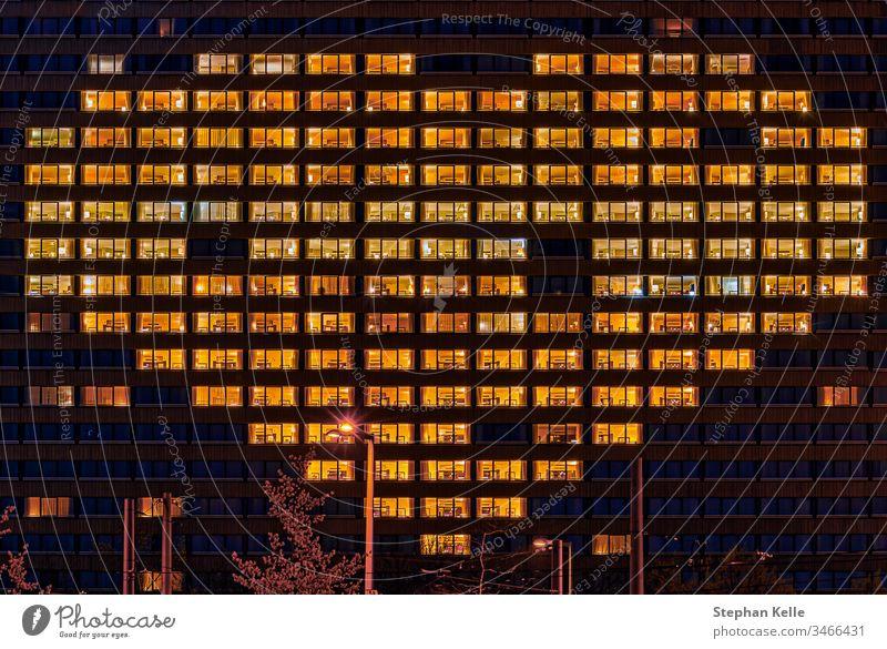 Herzförmige beleuchtete Fenster eines Gebäudes als Geste für Menschen, die andere unterstützen, wie jetzt in harten Coronavirus-Zeiten symbolisch. Form