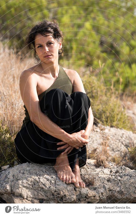 Eine vertikale Aufnahme einer schönen weiblichen Latina, die auf einem Felsen am Busch sitzt Frau Schönheit weiß Mädchen jung Natur hübsch Porträt Erwachsener