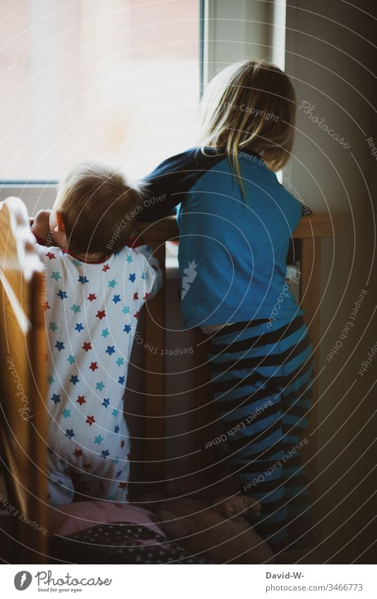 Kinder Geschwister schauen neugierig durchs Fenster Baby beobachten Bruder Mädchen klein Schwester Junge Kleinkind Schlafanzug schlafen wach Gitter niedlich