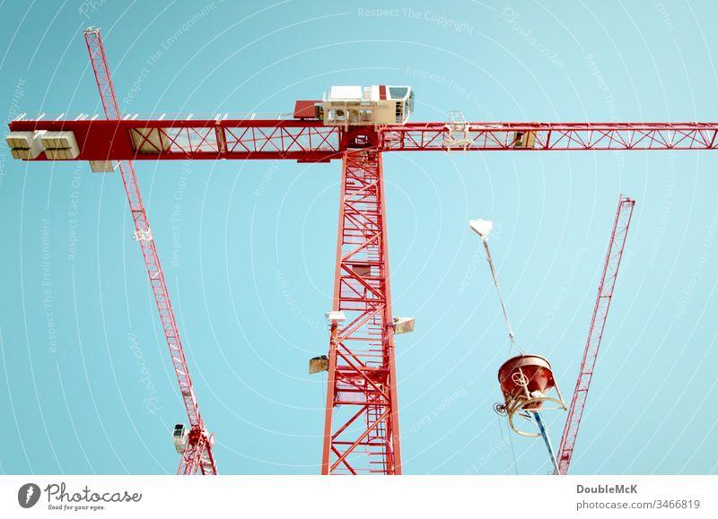 Drei rote Kräne mit einem Betonmischer vor blauem Himmel Kran Baustelle Außenaufnahme Farbfoto Arbeit & Erwerbstätigkeit Tag Stahl hoch Menschenleer