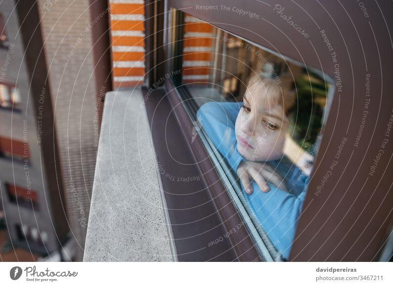 Trauriges Mädchen schaut aus dem Fenster traurig durch das Glas melancholisch Coronavirus Einsperrung covid-19 langweilig Traurigkeit durch das Fenster schauen