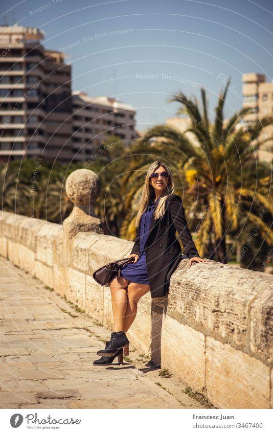 Junge glückliche Geschäftsfrau sitzt in der Stadt Erwachsener Teenager blond kolumbianisch Spanien Mädchen jung Frau attraktiv Tag stylisch elegant im Freien