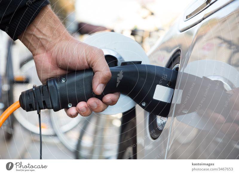 Elektroauto in Ladestation. PKW elektrisch Batterie Aufladen Betankung Stromleitung Auto ökologisch wiederaufladbar Alternative Energie urban Kraft Kabel