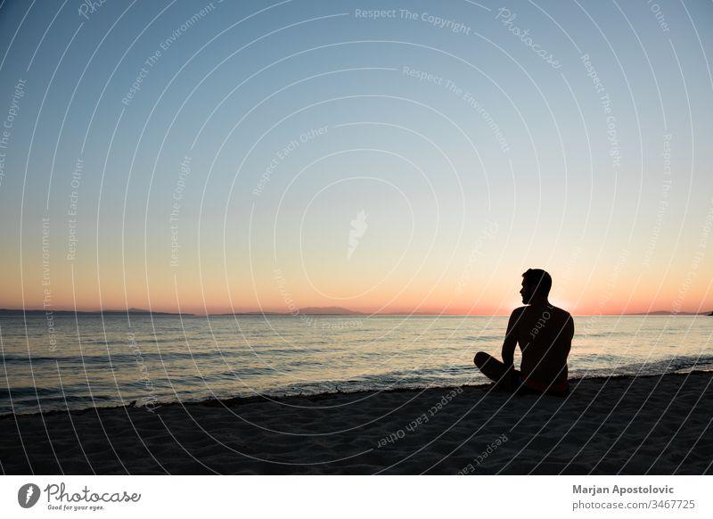 Junger Mann genießt Sonnenuntergang am Strand Erwachsener Abenteuer allein schön Windstille Küste Morgendämmerung Abenddämmerung genießend Freiheit Harmonie