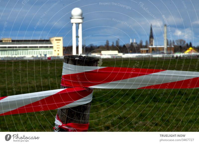 Corona Thoughts | Das Freizeitgelände Tempelhofer Feld ist mit rot weißem Absperrband markiert und im Hintergrund vor dunklem Wolkenhimmel leuchtet das markante Flughafengebäude im Sonnenlicht
