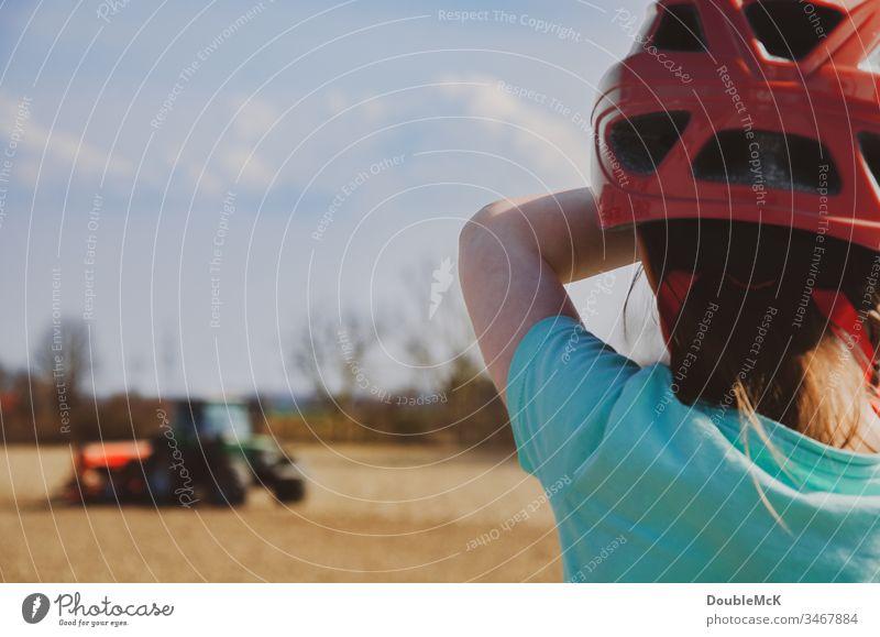 Mädchen mit rotem Fahrradhelm beobachtet Traktor auf dem Acker Träcker bulldog Landwirtschaft Feld Farbfoto Außenaufnahme Arbeit & Erwerbstätigkeit Natur