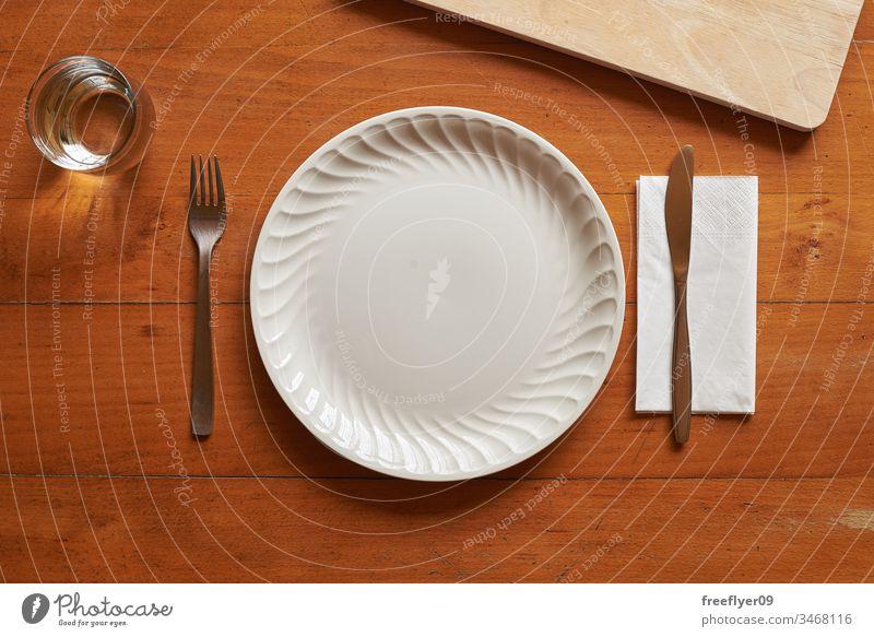 Porzellanteller und -besteck vor einem Hintergrund aus Holz Attrappe Flachlegung flache Verlegung Teller Küche Besteck weiß hölzern Tisch von oben Zenital leer