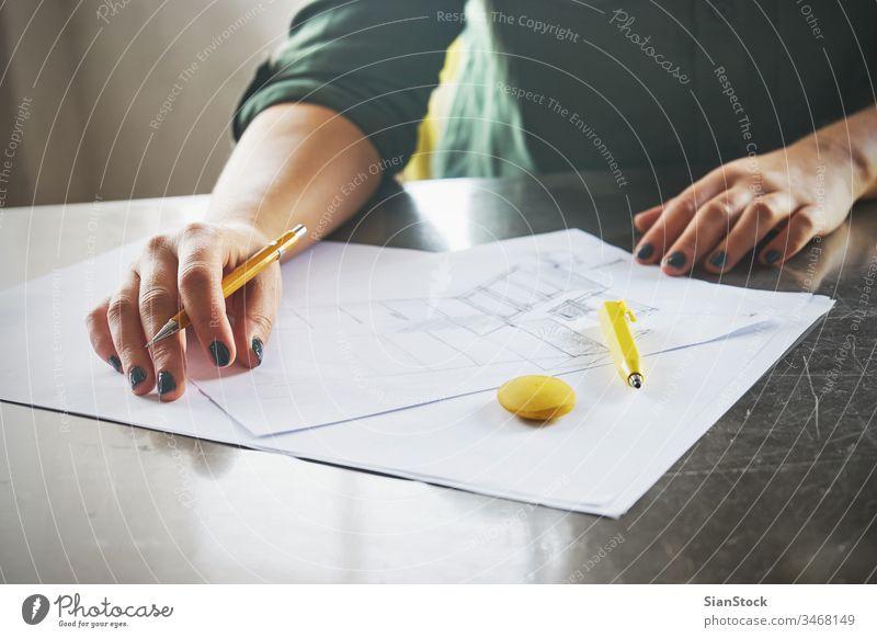 Architektin beim Skizzieren in ihrem Büro Business Arbeitsplatz Hände Schreibtisch Hand Tisch arbeiten Technik & Technologie Notebook Ansicht Kaffee nach oben