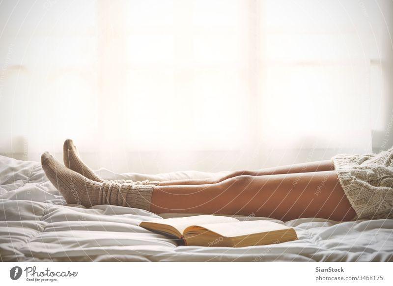 Weiches Foto von Frauenbeinen auf dem Bett mit einem alten Buch neben ihr lesen Fenster Ansicht LAZY Sonntag Winter Kaffee Tasse Tee Morgen Mädchen heimwärts