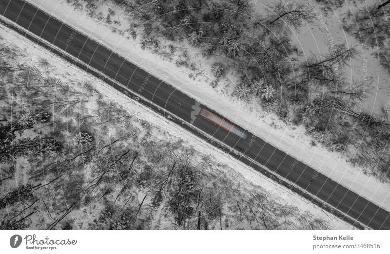 Luftaufnahme einer von Schnee umrahmten Winterstraße, ein Auto fährt als Langzeitbelichtung vorbei. Straße PKW diagonal Linie Lichter schwaebische Alb albstadt
